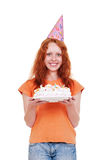 Smiley girl in funny cap holding cake Royalty Free Stock Photo