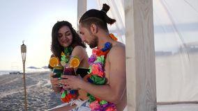 Smiley girl gives guy in hand cocktail on beach, summer holiday on tropical island, happy man and female to exotic stock footage