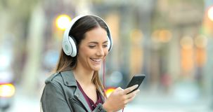 Smiley girl listening to music in the street stock video footage