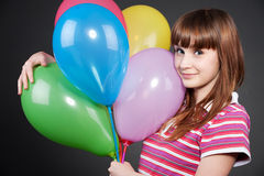 Smiley girl with motley balloons. Portrait of smiley girl with motley balloons Stock Image