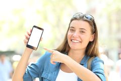 Smiley girl pointing to a blank smart phone screen. Mock up in the street Stock Image