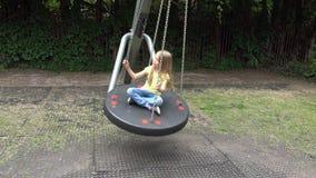 Smiley Girl Swinging Outdoor heureux, enfant jouant aux enfants 4K de parc de terrain de jeu banque de vidéos