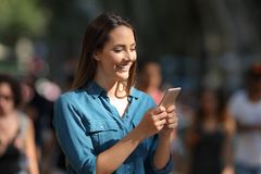 Smiley girl using a smart phone walking in the street Royalty Free Stock Photo