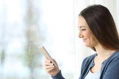 Smiley girl watching funny content in a smart phone. Beside a window in a rainy day Royalty Free Stock Photo