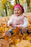 Smiley girl on yellow leaves Stock Images
