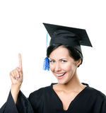 Smiley graduating student making the attention gesture. Graduating student in black academic gown and cap making the attention gesture, isolated on a white Royalty Free Stock Photo