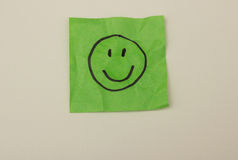 Smiley on green crumbled paper Stock Image