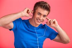 Smiley guy in earphones listening music on red background Royalty Free Stock Photos