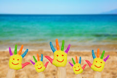 Smiley on hands against beach background. stock photography
