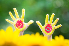 Smiley hands. Against green spring background Royalty Free Stock Image