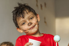 Smiley happy boy with painted face and lollipop in kids party Stock Image