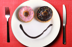 Smiley happy face made on dish with donuts eyes and chocolate syrup as smile in sugar and sweet addiction nutrition Royalty Free Stock Photo