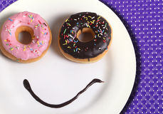 Smiley happy face made on dish with donuts eyes and chocolate syrup as smile in sugar and sweet addiction nutrition Royalty Free Stock Image