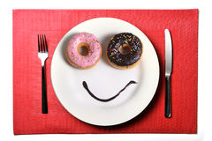 Smiley happy face made on dish with donuts eyes and chocolate syrup as smile in sugar and sweet addiction nutrition. Smiley happy face made on dish with donuts Royalty Free Stock Photo