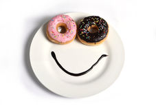Smiley happy face made on dish with donuts eyes and chocolate syrup as smile in sugar and sweet addiction nutrition. Smiley happy face made on dish with donuts Stock Photos