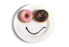 Smiley happy face made on dish with donuts eyes and chocolate syrup as smile in sugar and sweet addiction nutrition Stock Photo