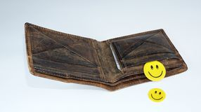 Smiley happy faces falling out of open leather wallet stock images