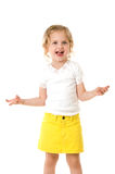 Smiley happy little girl wearing a yellow skirt on. Smiley happy little girl wearing a yellow skirt standing on white background Royalty Free Stock Photos