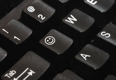 Smiley Key. Close-up of a computer keyboard, with a smiley face on one of the keys stock photos