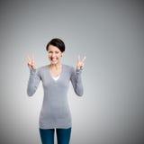 Smiley kobieta pokazywać zwycięstwa znaka z dwa rękami obrazy royalty free