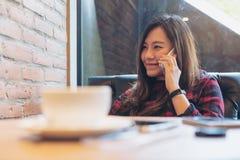 Smiley kobiety piękny Azjatycki obsiadanie na kanapie, używać i opowiadający na mądrze telefonie w nowożytnej kawiarni Obrazy Royalty Free