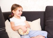 Little girl watching TV. Smiley little girl holding popcorn and watching TV Stock Image