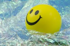 Smiley looking up. Happy yellow smiley face looking up over a bright pearly background Royalty Free Stock Photo