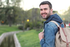 Smiley male holding backpack outdoors with copy space.  Royalty Free Stock Photo