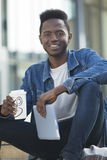Smiley Male Student. A happy young student smiles at the camera as he takes a break from studying with a hot drink. He is sitting outdoors holding his digital Stock Photo