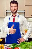 Smiley man in blue apron showing thumbs up Stock Image