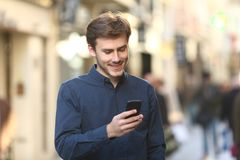 Smiley man checking smart phone content in the street royalty free stock photo