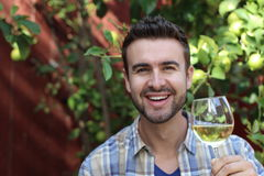 Smiley man holding a glass of white wine. Man smiling with his glass of wine Stock Photography