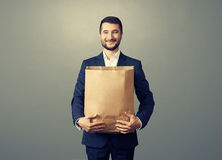 Smiley man holding paper bag over dark Royalty Free Stock Images