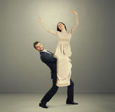 Smiley man holding young beautiful woman Royalty Free Stock Photos