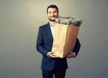 Smiley man with money over grey Royalty Free Stock Photography
