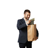 Smiley man with paper bag and money Royalty Free Stock Photos