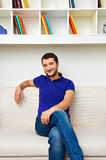 Smiley man sitting on sofa and resting Royalty Free Stock Photos