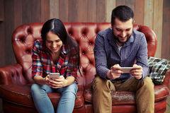 Smiley man and woman using smartphones Royalty Free Stock Photography