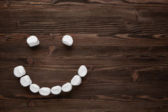 Smiley marshmallow on a dark background. Smiley marshmallow on a dark wooden background Royalty Free Stock Photo