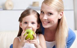 Smiley mom with her eating apple daughter Royalty Free Stock Image