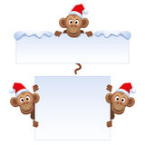 Smiley monkey head in Christmas red hat peeking from behind a blank banner. Stock Photos