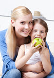Smiley mum with her eating apple daughter Stock Images