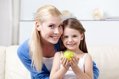 Smiley mummy with her keeping apple daughter Royalty Free Stock Image