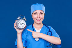 Smiley nurse pointing at alarm clock Royalty Free Stock Images
