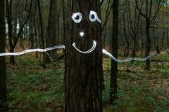 Smiley op boom in bos stock afbeeldingen