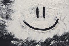 Smiley på vitt vetemjöl på abstrakt begreppsvartbakgrund Fotografering för Bildbyråer