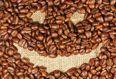 Smiley painted on coffee beans, horisontal view. Cheerful smiley painted on roasted coffee beans, horisontal background Stock Images