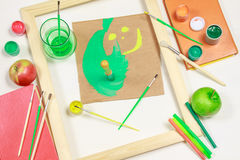 Smiley with painting equipments. Wooden frame with a smiley and painting equipments on the white surface stock photography