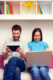 Pary obsiadanie na kanapy i mienia komputerach zdjęcia stock