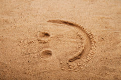 Smiley picture on a beach sand. Shallow DOF Royalty Free Stock Photography